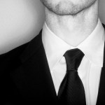 Close up of an unshaved man wearing a black suit and black tie